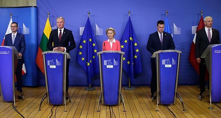 Fem personer står bredvid varandra. De har varsin talarstol. I mitten står en kvinna. De andra fyra är män.