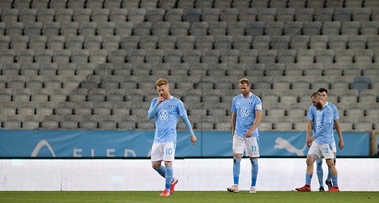 Bilden visar en stadion för fotboll. Några spelare går på gräset. De hänger med sina huvuden och ser ledsna ut. De har ljusblå tröjor och vita shorts.