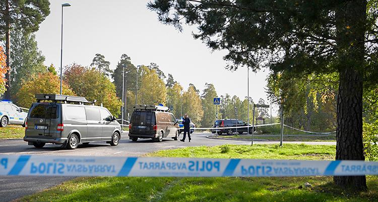 Bilden är tagen utomhus. Poliserna har satt upp ett band för att spärra av. Bakom bandet syns flera polisbilar. Runt vägen finns gräsmattor och träd.