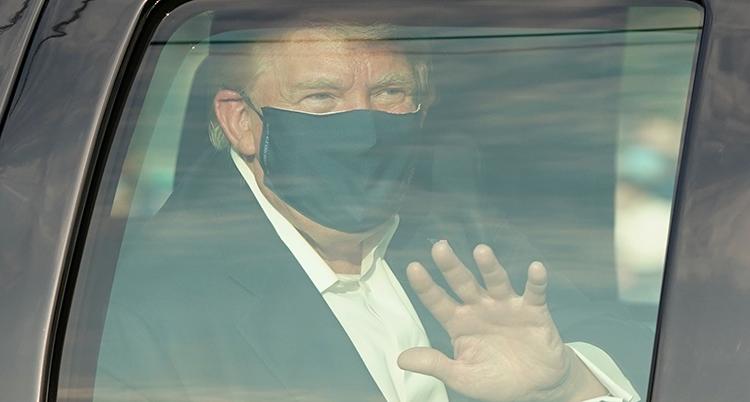 Donald Trump syns genom en bilruta. Han har mask för näsa och mun och vinkar.