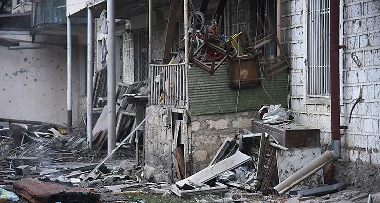 Vi ser utsidan på ett hus. Huset ser trasigt ut. Utanför huset ligger massor med skräp och trasiga saker.