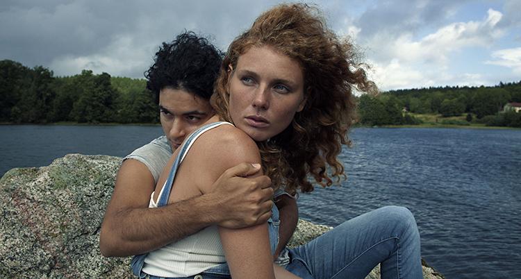 Två personer sitter utomhus vid en sjö. Killen har mörkt hår. Han håller om en tjej. Hon har rött hår.