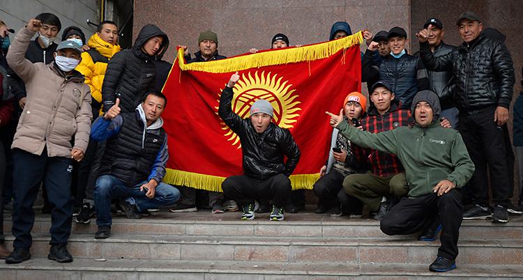 Flera män står eller sitter på en trappa. De gör tummen upp. De har en stor flagga som är röd men en gul symbol i mitten.