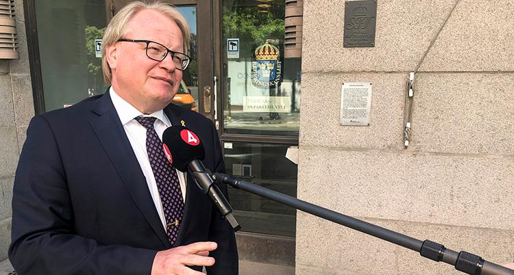 Peter Hultqvist utomhus står och svarar på frågor framför en mikrofon som det står tv4 på.