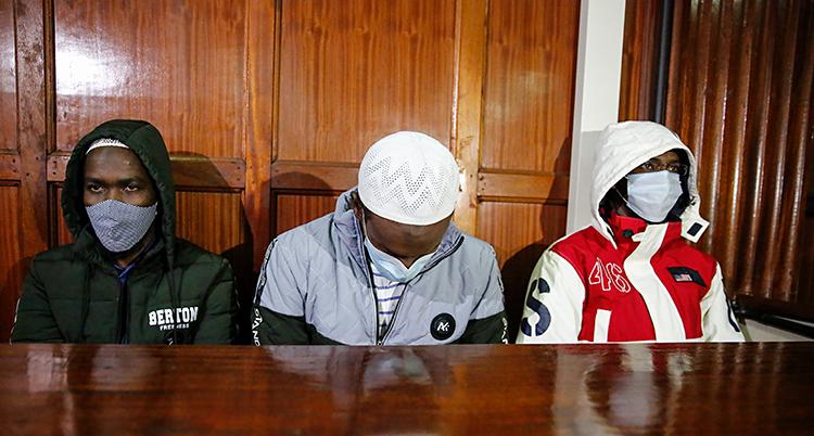 Tre män sitter i en sal. De sitter bakom ett bord. Alla tre har munskydd på sig.