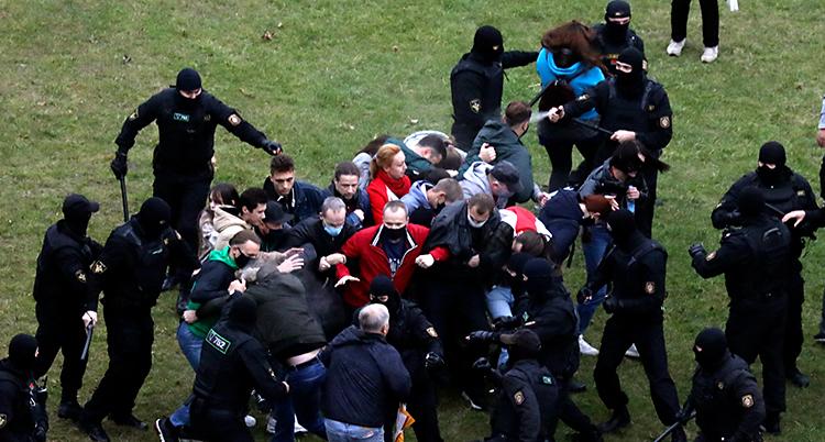 Flera personer står i en klump på en gräsmatta. Runt dem finns poliser i svarta kläder och svarta masker.