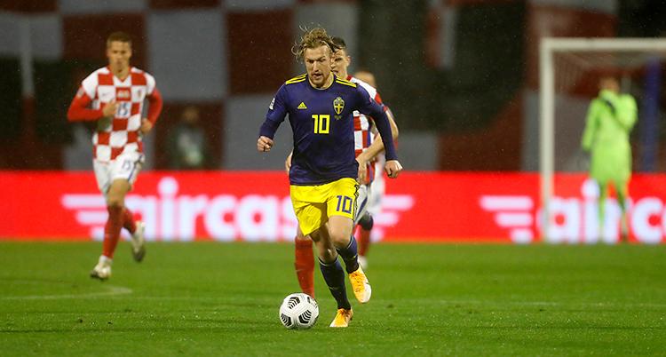 Från en match i fotboll. En svensk spelare springer med bollen. Han har blå tröja och gula shorts. Han blir jagad av en kroatisk spelare i röda och vita kläder.