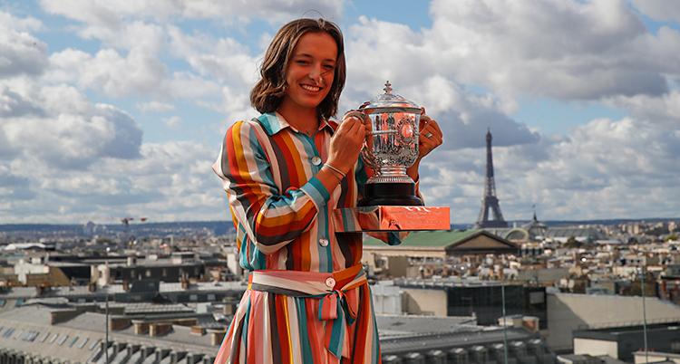 Hon står utomhus. Hon håller i en pokal. Hon har en klänning som är randig i flera färger. I bakgrunden syns Eiffeltornet.