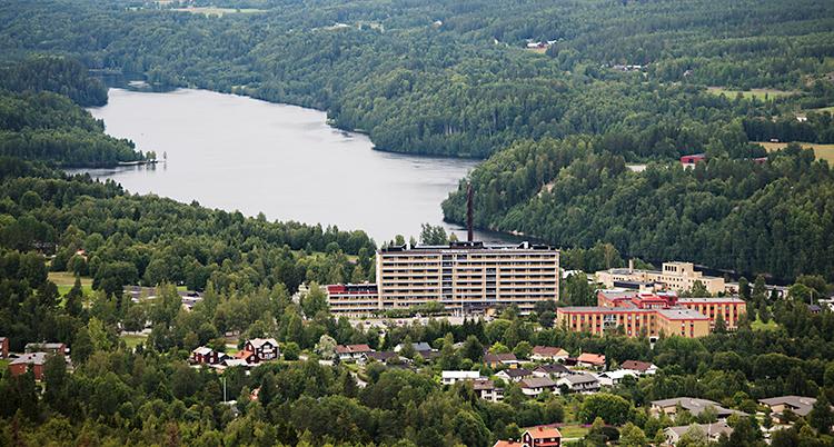 Bilden visar Sollefteå. Bilden är tagen från ett berg. Vi ser sjukhuset och många andra hus. I bakgrunden syns skog och vatten.