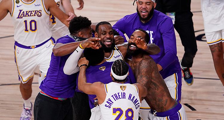 Bilden är från en basketplan. Flera personer kramas och är glada.