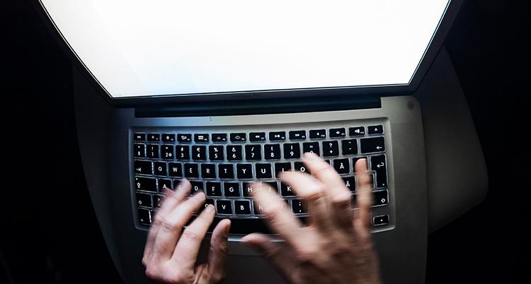 Händer skriver på ett svart tangentbord