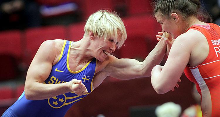 Två kvinnor brottas. Jenny Fransson har blå dräkt och ljust hår. Den andra har röd dräkt och brunt hår.