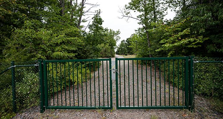 Ett staket spärrar av en väg. Staketet är ungefär en meter högt. Bredvid vägen finns skog.