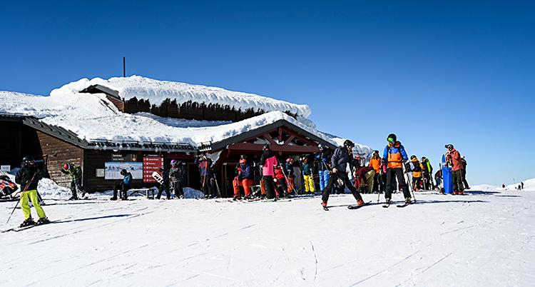 Vi ser ett hus uppe på ett fjäll. Det är snö. Solen skiner. Folk åker slalomskidor utanför huset.