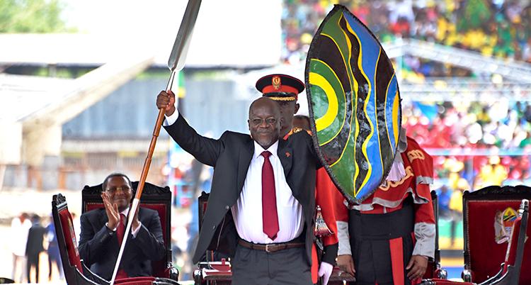 En man har vunnit valet till president. Han håller upp en sköld och ett spjut. De är symboler när du vunnit valet.
