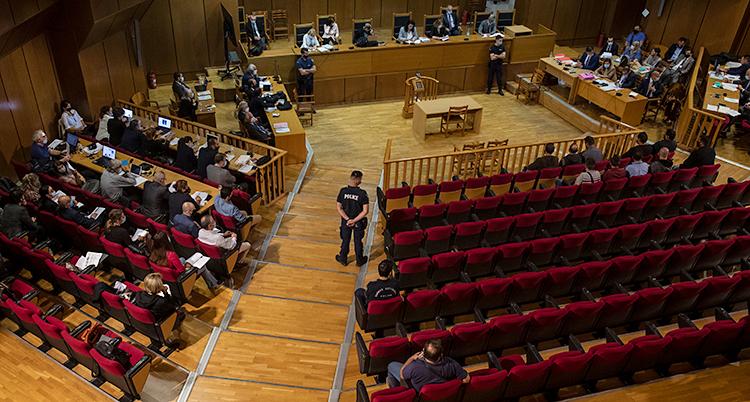 Vi ser en stor sal. Bilden är tagen uppifrån. På bänkarna sitter människor. En polis står och vaktar.