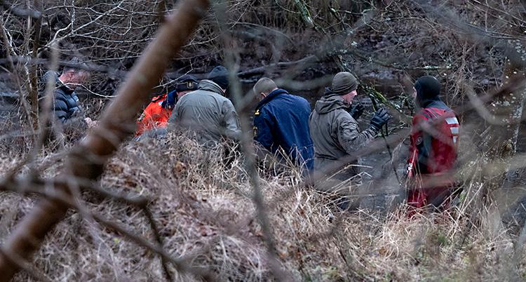Flera poliser står vid en å. En av dem har dykarkläder. Det är buskar och gräs runtomkring.