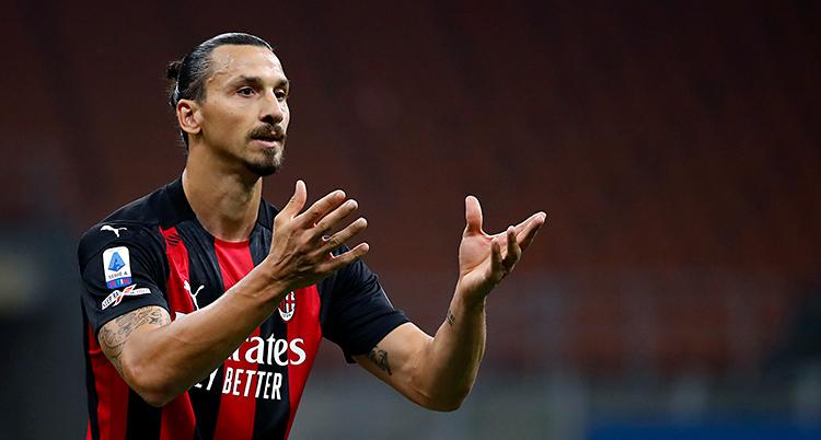 Zlatan har en randig tröja i rött och svart. Han har håret i en knut bak på huvudet.