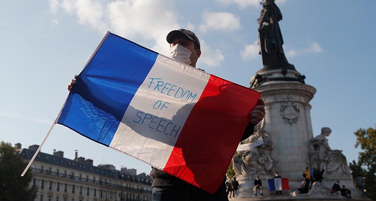 En man som protesterar i Paris håller upp en flagga där det står freedom of speech.