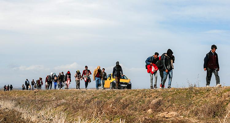 Ett tiotal personer går på rad på en höjd. De ser ut att vara människor på flykt.