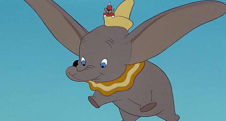 En tecknad elefant. Elefanten flyger med sina öron. Elefanten har en hatt där det sitter en mus.