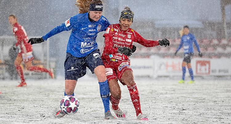 En match i fotboll. Två spelare kämpar om bollen. Det faller snö. Och det är snö på planen.