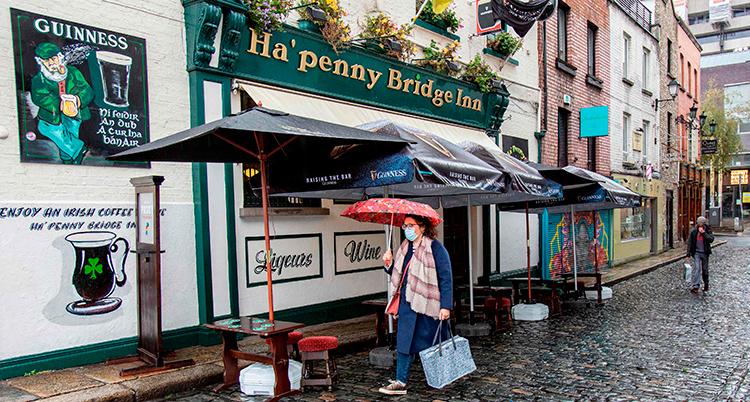 En person går med ett paraply på en regntung gata på Irland. Personen har munskydd och ett paraply över huvudet. I bakgrunden en irländsk pub.