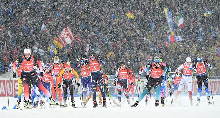 Flera åkare som åker skidor på en stadion. De har gevär på ryggen. I bakgrunden finns en massa publik. Det snöar.