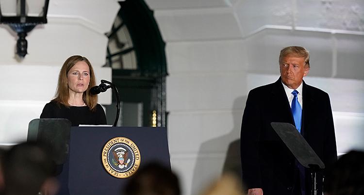 Amy Coney Barrett står på en scen och pratar. Hon står vid en talarstol och pratar i en mikrofon. Till höger i bilden står Donald Trump.