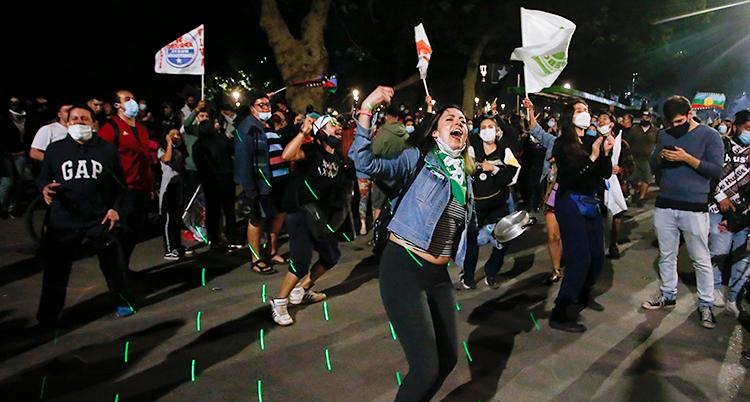 Det är kväll. Unga människor är ute på gatorna. De har flaggor. Många ser glada ut.