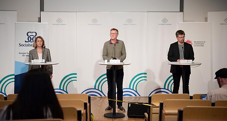 Tre personer står på en scen. De pratar i varsin mikrofon. Längst till vänster står en kvinna. De andra två är män.