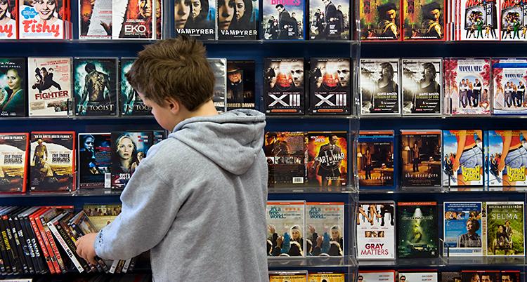 En pojke står och tittar vid en hylla. På hyllan finns det en massa olika dvd-filmer.