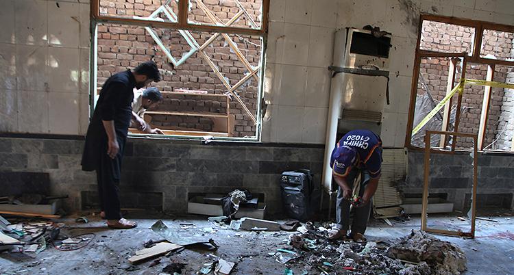 Två personer undersöker ett rum i ett hus. Det har hänt en explosion i huset. Det ligger trasiga saker på golvet.