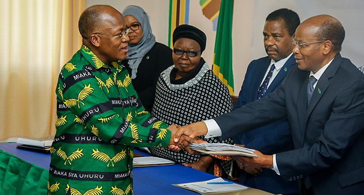 Fem personer är i bilden. En man med en färgglad skjorta står till vänster. Han tar i hand med en man i kostym.