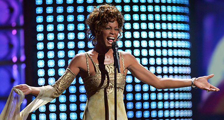 Hon står på en scen och sjunger. Hon har en klänning som ser ut som guld. I bakgrunden lyser lampor i blått och lila.