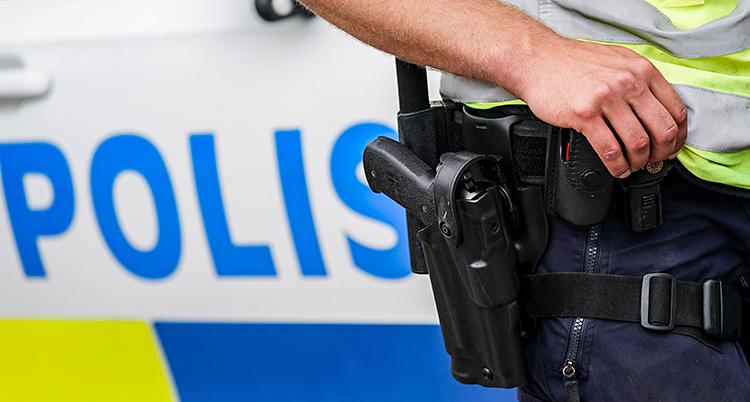 Bilden visar en polis. Vi ser bara armen och pistolen. I bakgrunden syns en polisbild. Det är inte polisen på bilden som nyheten handlar om.