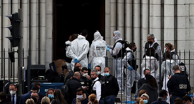 Flera poliser står utanför en kyrka. Några av dem har skyddskläder på sig.