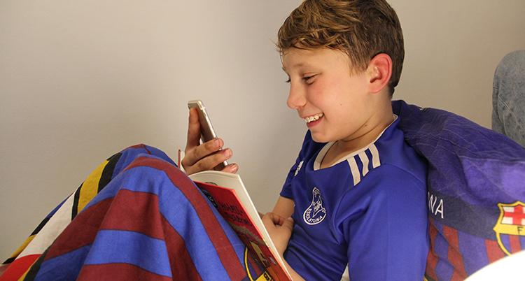 Harry Larsson-Marjamäki lsitter i sin säng med en bok och en mobil.
