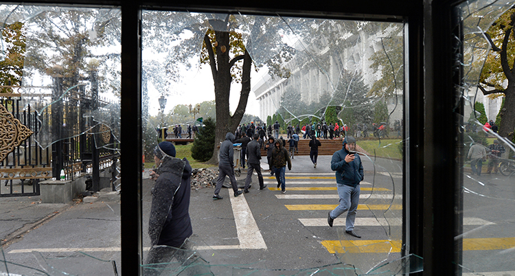 Flera personer syns genom en krossad glasruta.