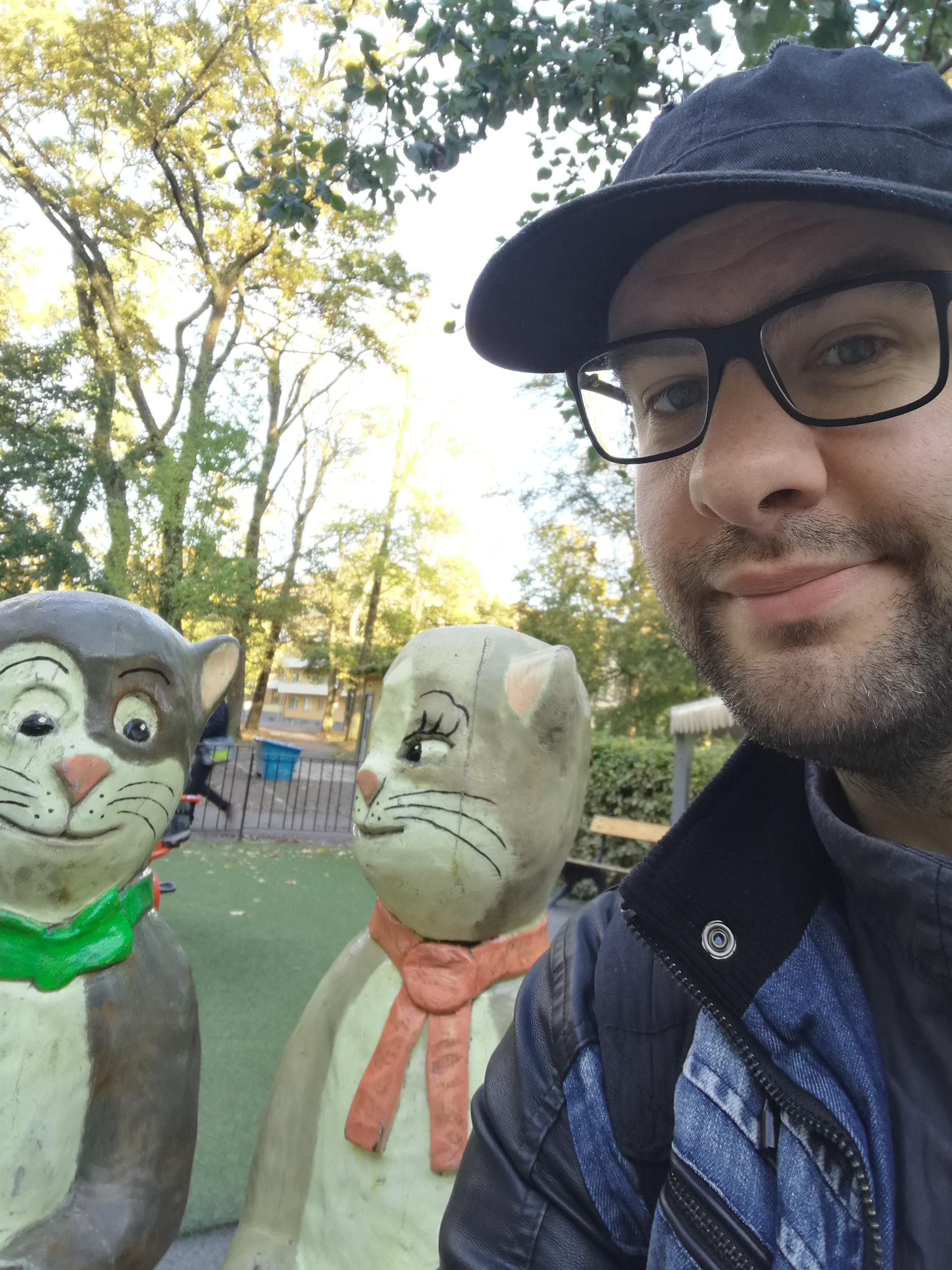 Han tittar in i kameran. Han har glasögon och keps. I bakgrunden syns statyer av Pelle Svanslös och Maja Gräddnos.