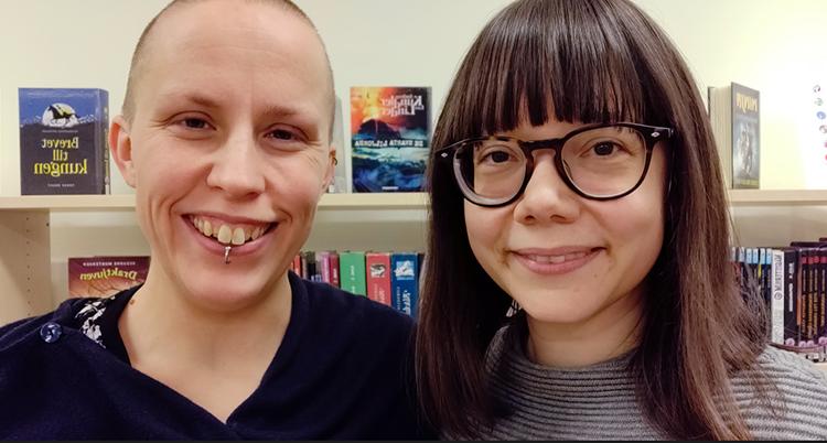 De står bredvid varandra. Sanna har inget hår. Hon ler och har en piercing i läppen. Malene har glasögon och mörkt långt hår. Bakom dem syns böcker.