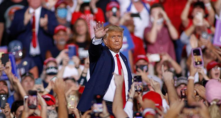 Han vinkar till sina väljare. Massor av människor står runt honom.