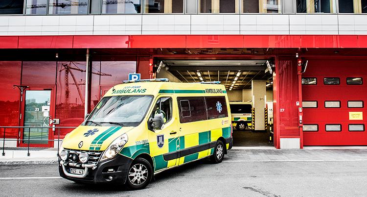 En ambulans står utanför röda portar.
