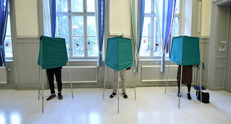 tre personer står bakom tre röstbås i en sal. Vi ser bara deras ben.