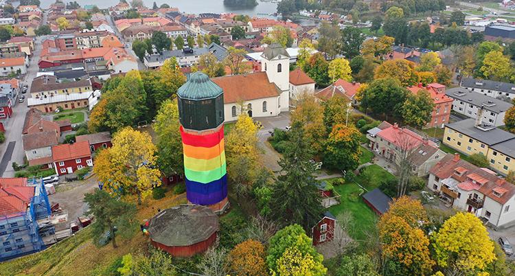 Ett torn invirat i en stor flagga i regnbågens färger.
