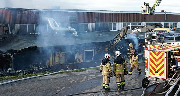 Tre brandmän står utanför stationen. Massor av rök syns runt den huset som är svart av sot.