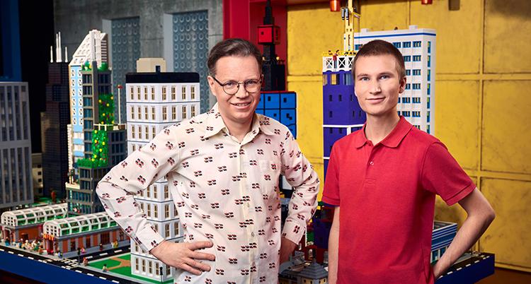 De står bredvid varandra. Den ena har vit skjorta. Den andra röd t-shirt. Bakom dem syns ett stort bygge av lego.