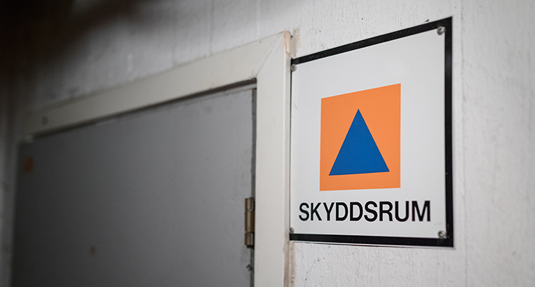 En bild på en skylt med en orange fyrkant. I den är en bli triangel.