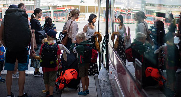 En grupp människor är på väg att gå in i en buss.
