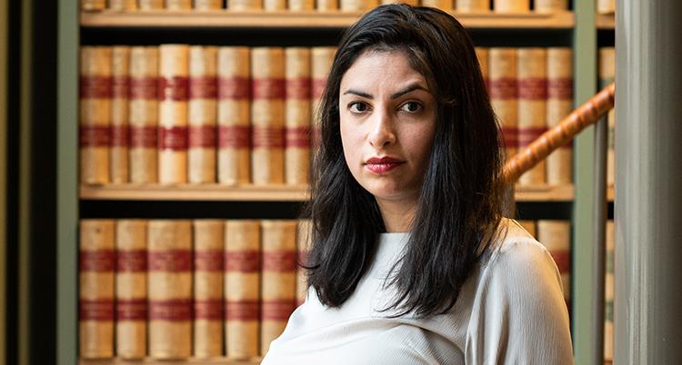 Ett porträtt på henne. Hon står framför en bokhylla med likadana bruna böcker. Det ser ut som uppslagsböcker.